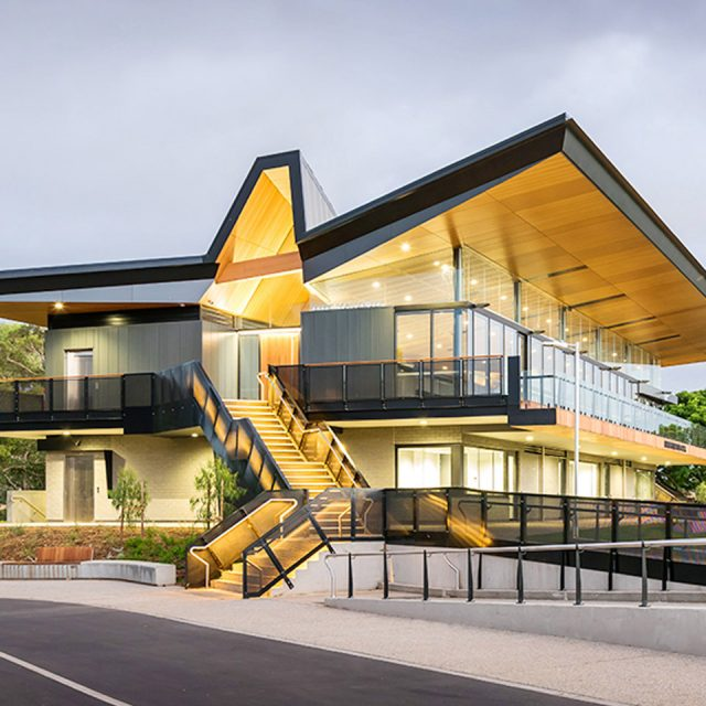 The new Karen Rolton Oval facility for SACA - wide shot of staircase and pitched roof lit up at dusk.